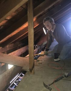 Museum volunteer Paul Waehler removes post-Shaker boards in the Laundry attic. Enfield Shaker preservation.