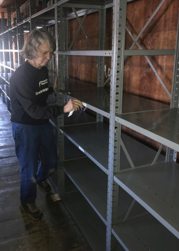 Lynn Waehler removes old labels from the shelves. Enfield Shaker preservation.