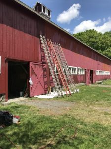 1854 Cow Barn showing ladders and painting in progress. Enfield Shaker preservation.