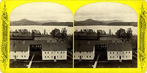 Stereoview at Enfield, NH Shaker Village - Looking north, Brethren's shops, Garden and Mascoma Lake in the foreground.