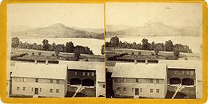 Stereoview of Enfield, NH Shaker Village - Brethren's West Shop, Wood House, and Cemetery, with Mascoma Lake in the background.