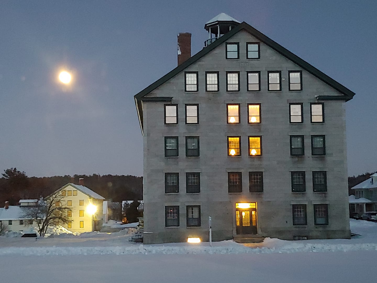 Winter evening scene of Enfield Shaker Museum's Great Stone Dwelling, featuring snowy landscape and full moon in the night sky